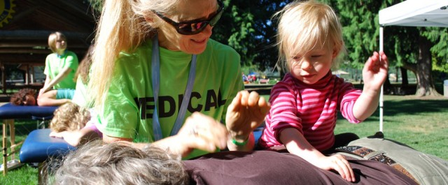 Christine Sutherland volunteering to teach kids massage at Lakeside Park in Nelson, BC